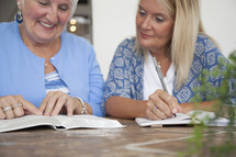 women discussing scripture and writing in a journal at a Bible study