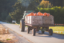 a tractor and wagon of pumpkins