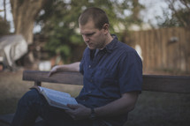 A young man sitting on a bench reading the Bible