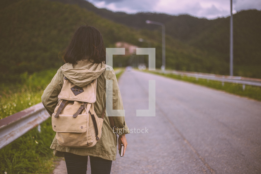 a woman walking alone down a road