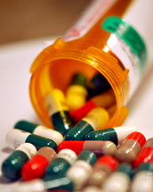 Bright colored medicine capsules spilling from a prescription container.