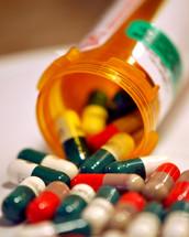 Bright colored medicine capsules spilling from a prescription container.