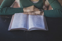 A woman sitting at a table and reading the Bible