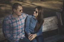A young couple wearing sunglasses smiling
