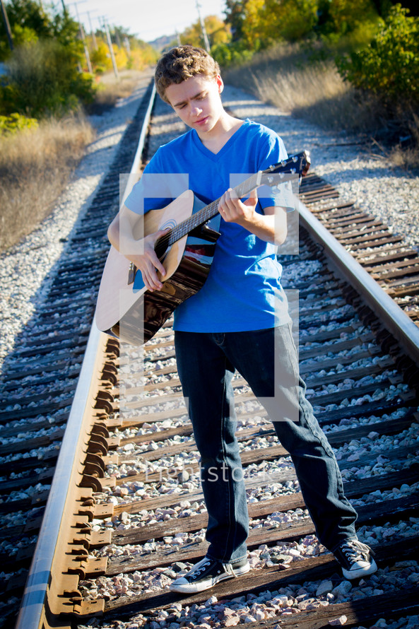 teen boy playing a guitar on railroad tracks