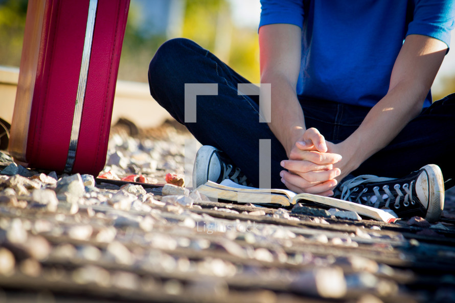 man sitting on the ground praying with a Bible
