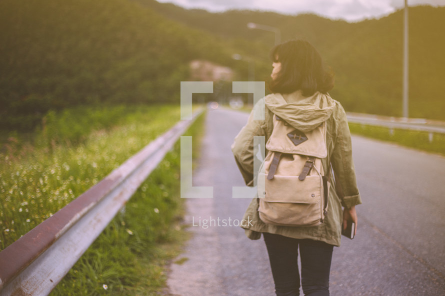 a woman walking alone down a road carrying a Bible