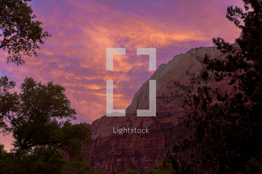 red rock mountains at sunset and pink and purple clouds in a sky