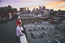 two young men dangling their legs over the roof of a building