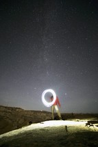 A man making a circle of light under a starry sky.