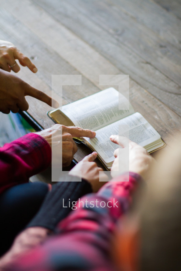 Hands pointing at a scripture verse in an open Bible