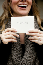 woman holding a notecard with the words I Love You