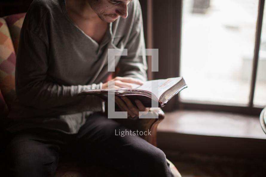 a man reading a Bible in front of a window
