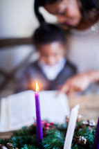 mother and son reading a Bible by an Advent wreath