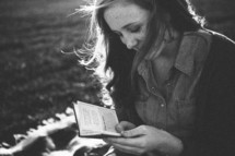 teen girl sitting on a blanket reading a pocket Bible