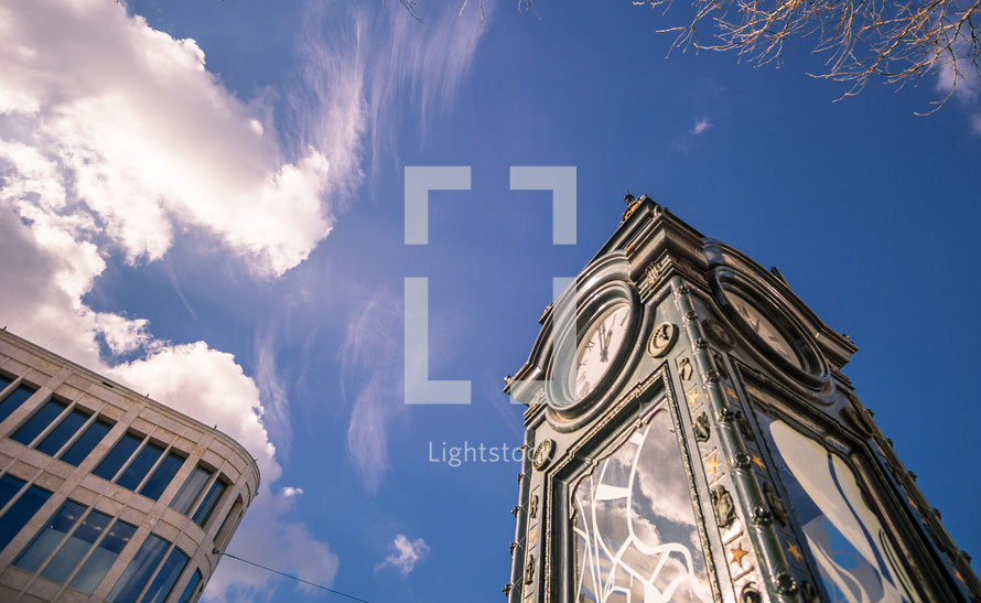 looking up at a clock tower against a blue sky