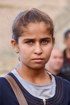 Face of a stoic green eyed teenage Yazidi girl