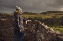 A woman in a winter coat looking out over a stone wall at green rolling hills