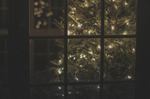 A lighted Christmas tree through a window
