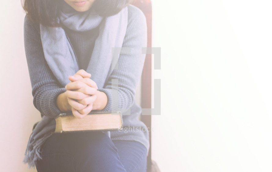 a woman praying over a Bible sitting in a chair