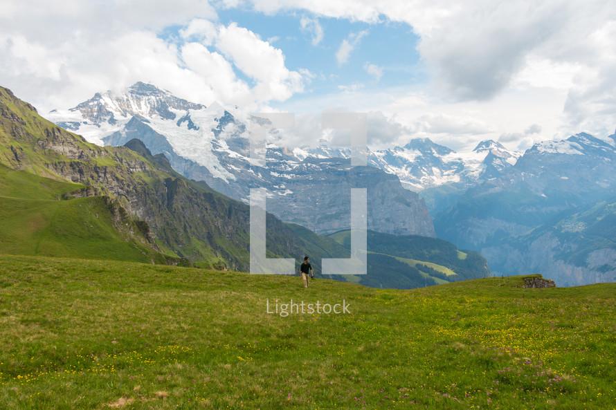 a man walking on a green mountain