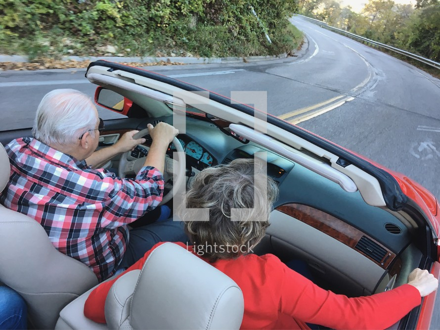 An elderly couple driving a red convertible on a curvy road