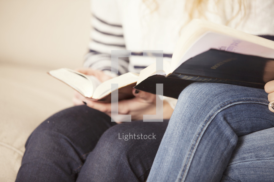women sitting on a couch reading Bibles together.