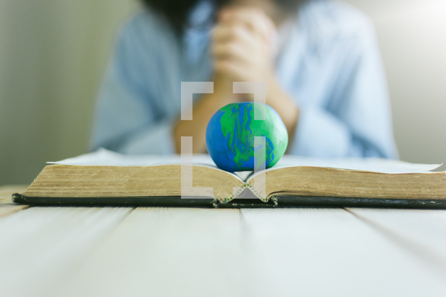 globe on the pages of a Bible and praying hands
