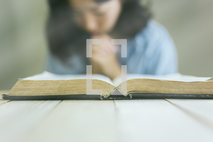praying in front of a Bible