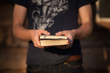 man holding a Bible and journal