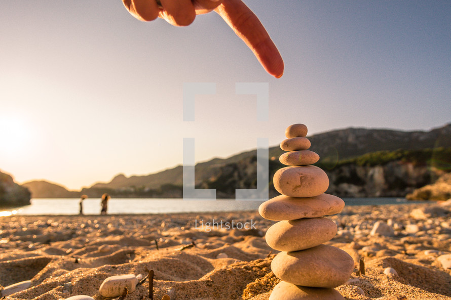 hand stacking smooth stones