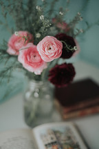 vase of pink flowers and opened book