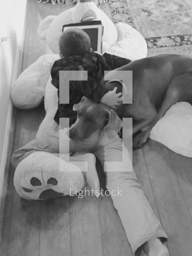 A boy playing on an iPad and lying on a large teddy bear on the floor with his pet dog