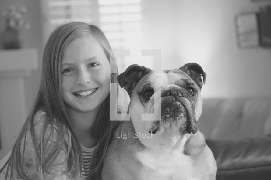 a little girl posing with her pet bulldog