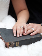 Husband and wife's hands on a tattered Bible.