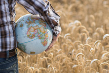 man holding a globe standing in a field