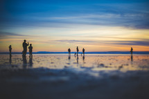 people standing on a beach at sunset
