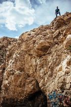 A man standing atop a cliff.