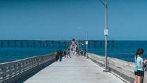 people on a pier at a beach