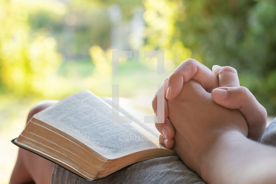 a person praying with a Bible outdoors