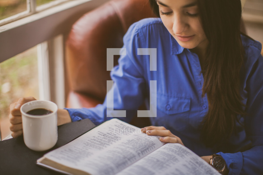 A woman drinking coffee and reading a Bible