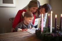 a family reading a Bible near an Advent wreath