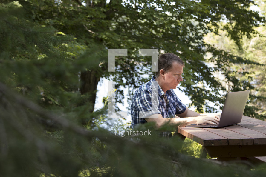 Middle aged man working on laptop computer in rural wooded environment in woods