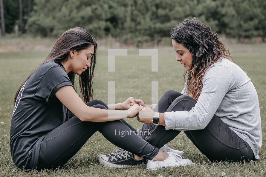 friends holding hands in prayer