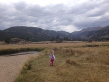 a toddler girl walking in a prairie