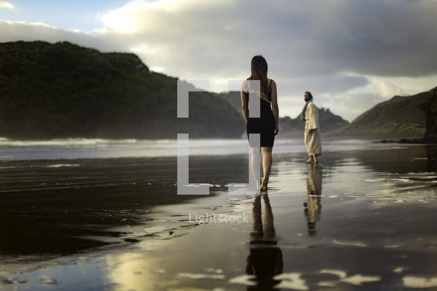 A woman standing on a beach and Jesus looking back at her