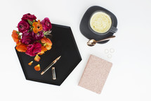 pen, tray, rose petals, notepad, and bowl of soup on a white table