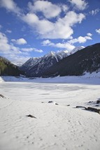snow on a frozen lake in a valley