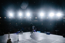 Stage lights shining on a man speaking on a stage before an audience.
