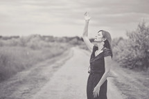 woman standing on a dirt road with a hand raised to praise God
